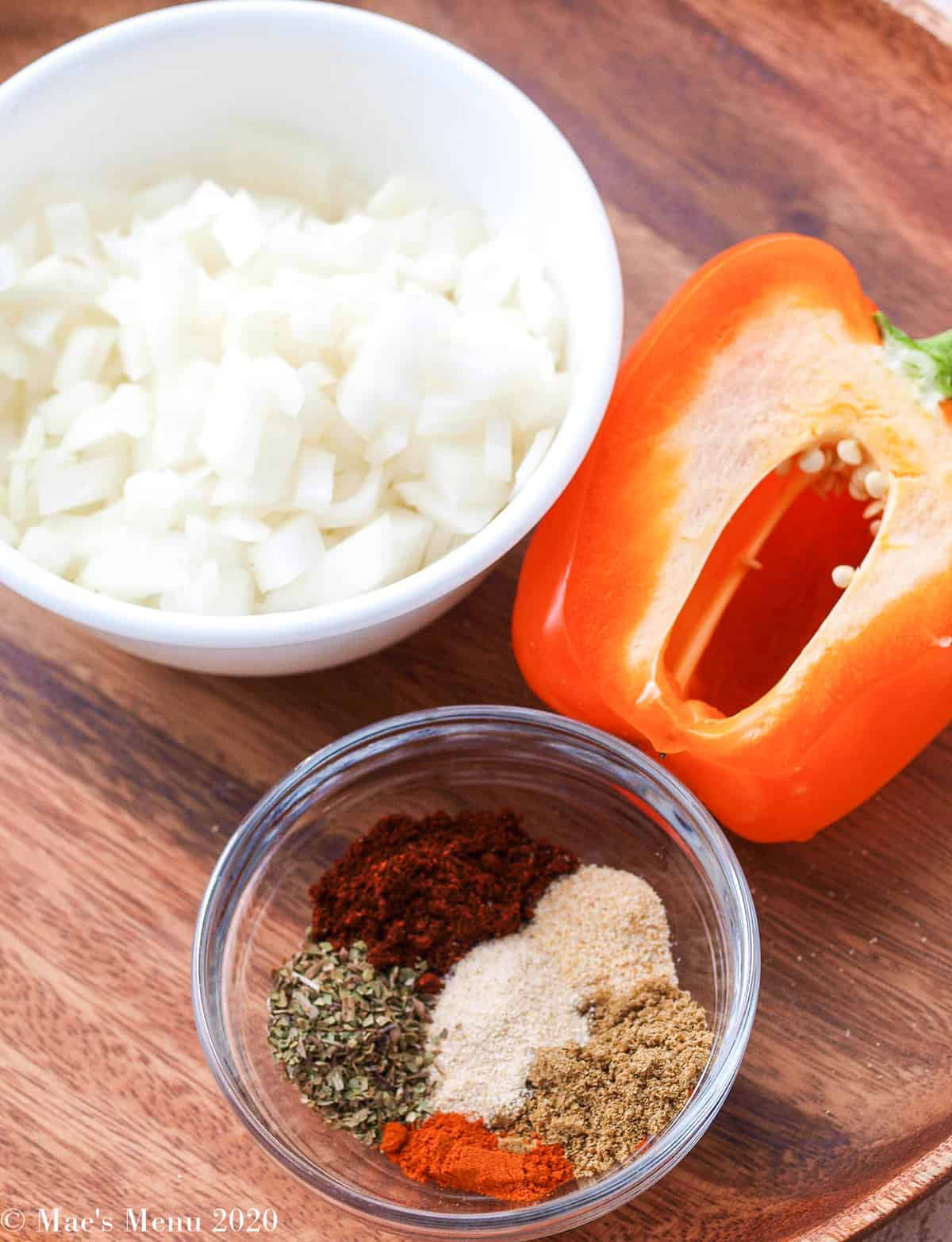 Chopped onions, half a pepper, and a small dish of spices for homemade taco seasoning.