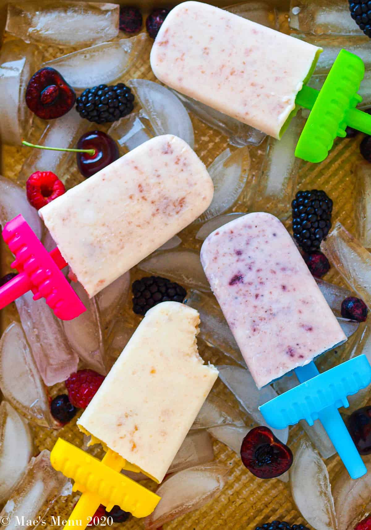 four yogurt popsicles on a tray of ice cubes with berries and cherries around them. One bite is taken out of the peach popsicle