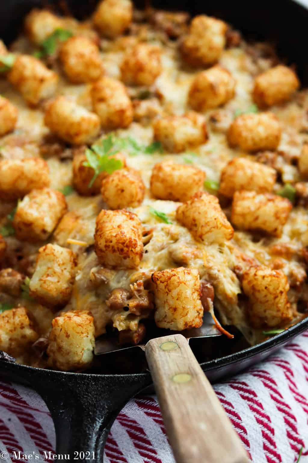 A side shot of a cast iron skillet full of taco tater tot casserole with a serving spoon in it