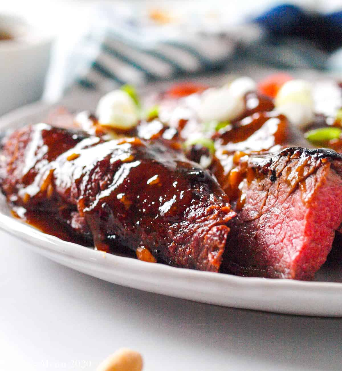 a side shot of a plate of sliced tri-tip  with soy sauce glaze and green onions on top.