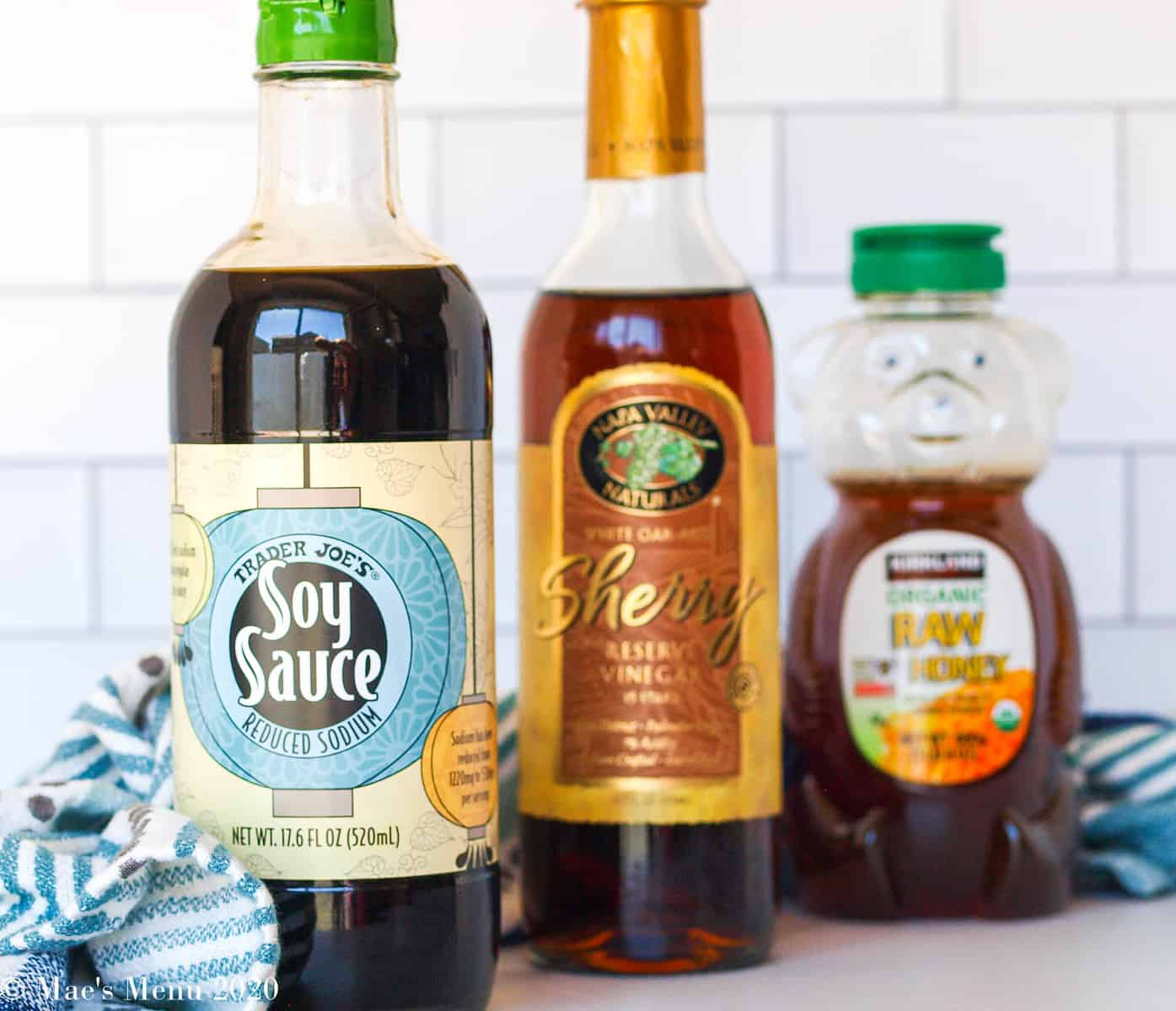 A bottle each of soy sauce, sherry vinegar, and honey