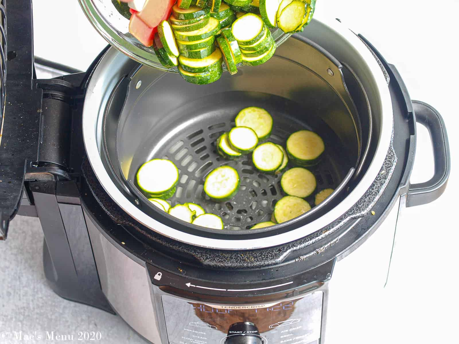 pouring zucchini slices into the basket of an air fryer