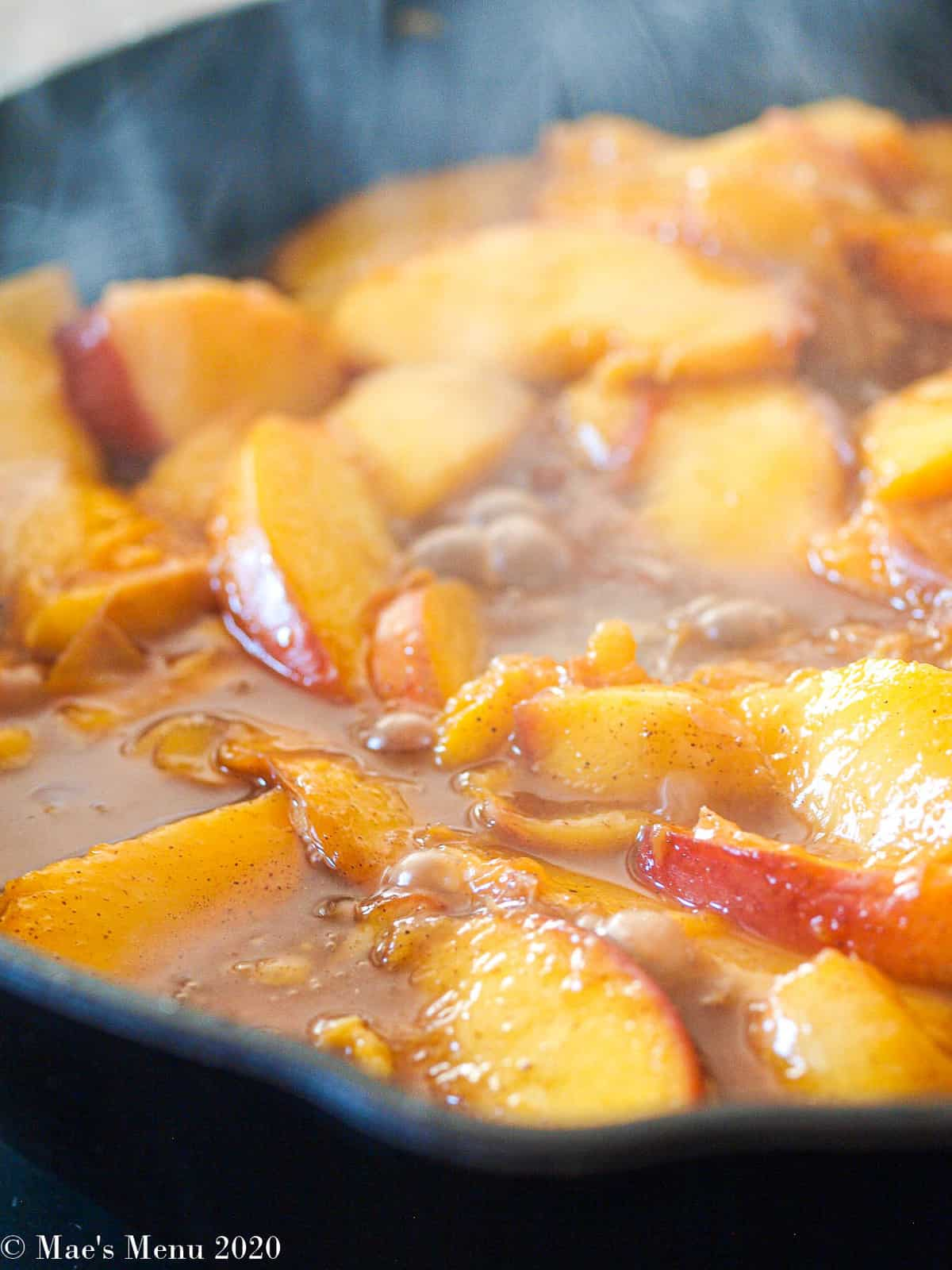 An up-close shot of peaches cooked down and bubbling.