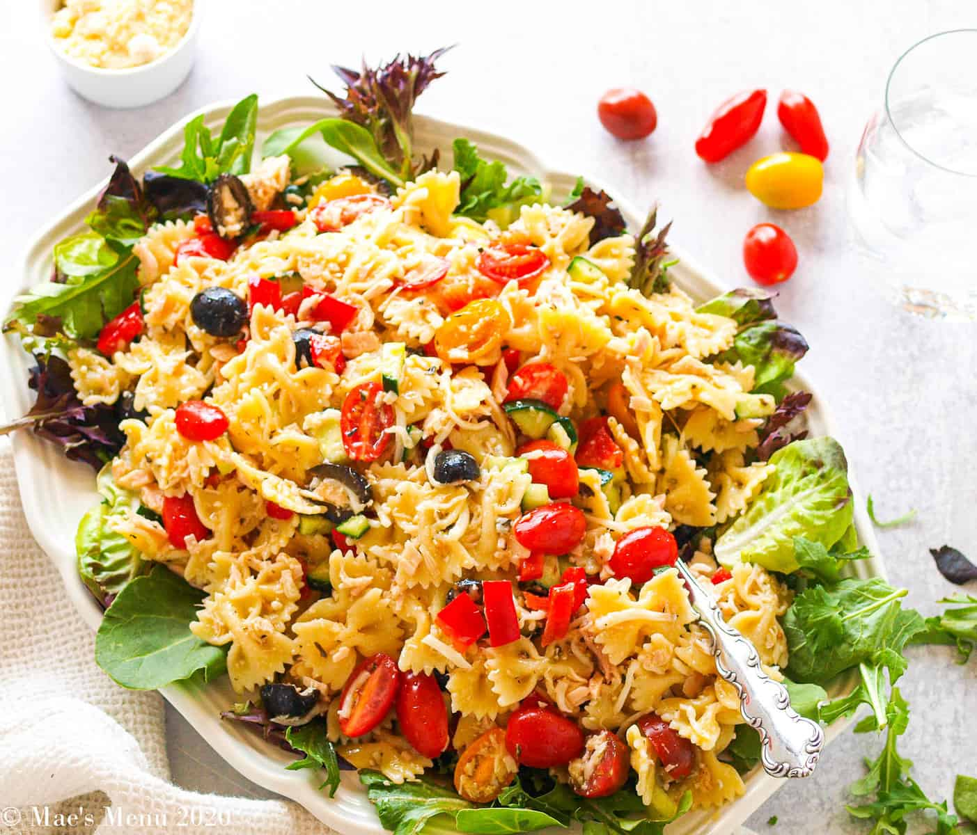 An overhead shot of a large platter of Italian Tuna Pasta salad with tomatoes, a glass of water, and a cup of cheese next to the platter.