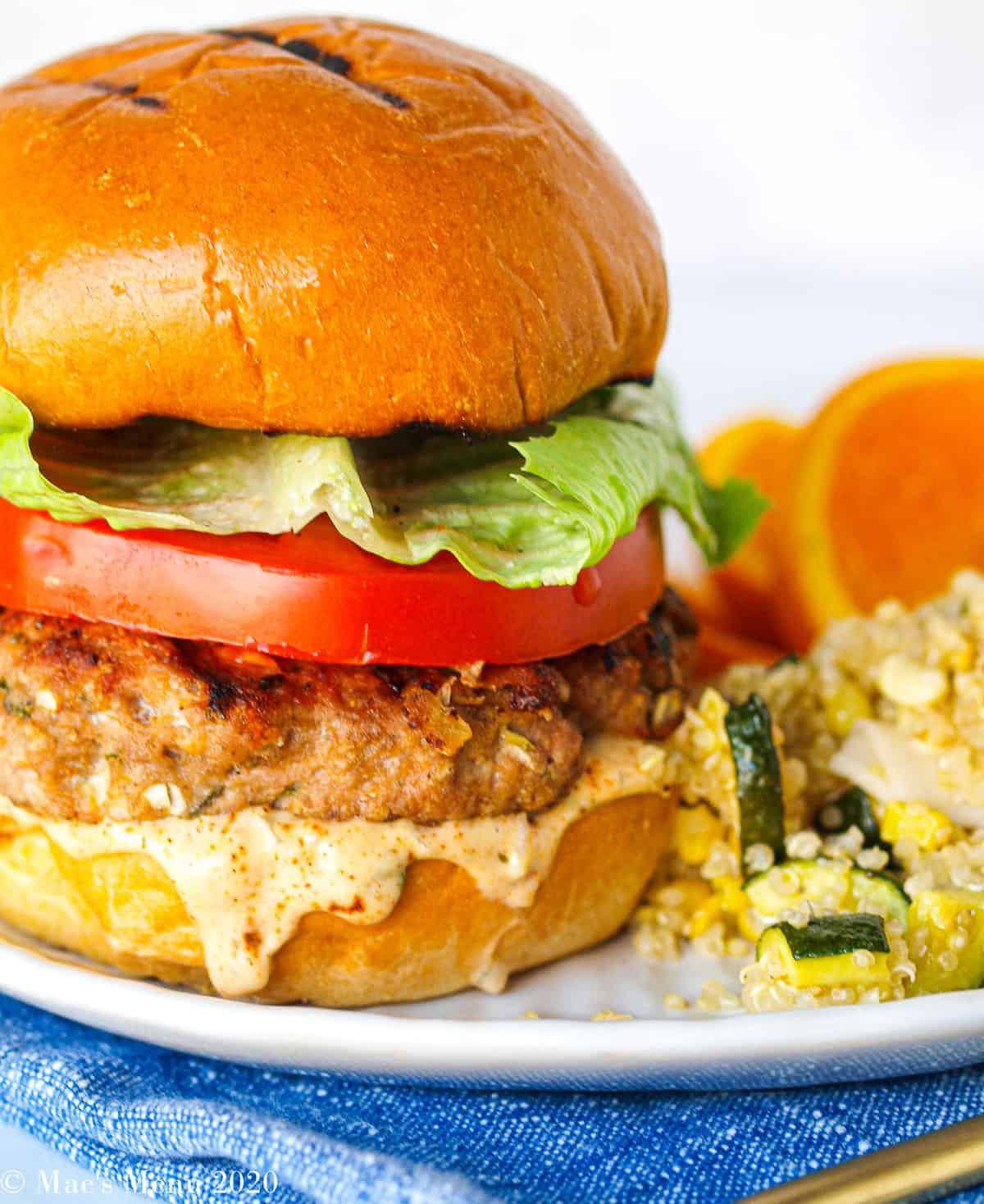 A jamaican jerk turkey burger on a white plate with quinoa and oranges.