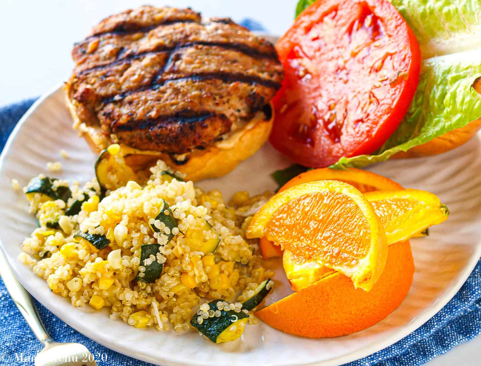An open-faced Jamaican Jerk Turkey Burger on a white plate with quinoa salad and sliced oranges