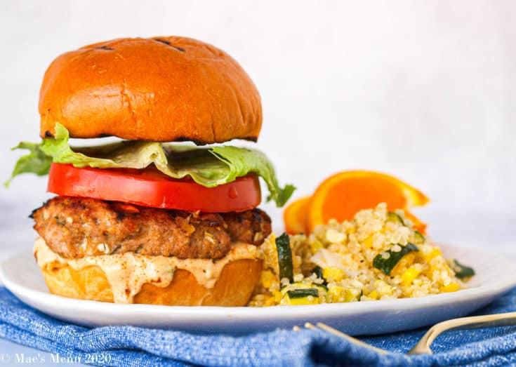 A large Jamaican jerk turkey burger on a white plate next to quinoa salad and oranges.