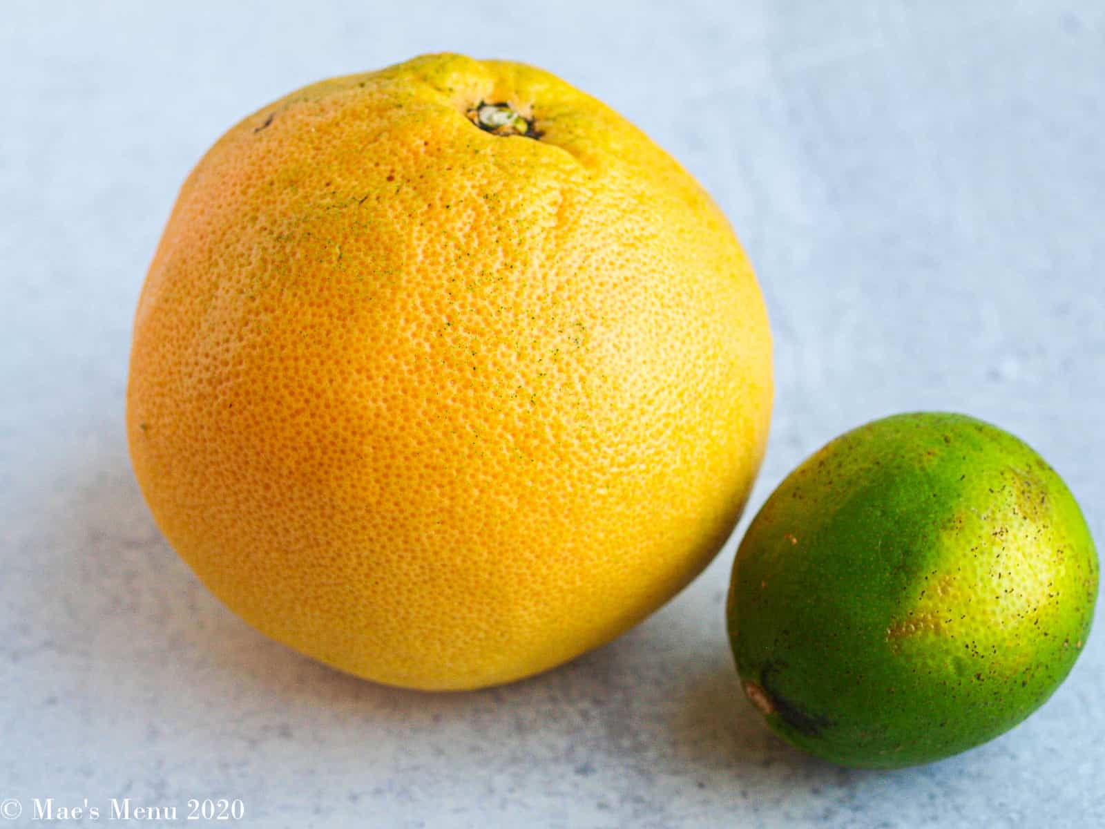 A large grapefruit and a lime sitting side-by-side