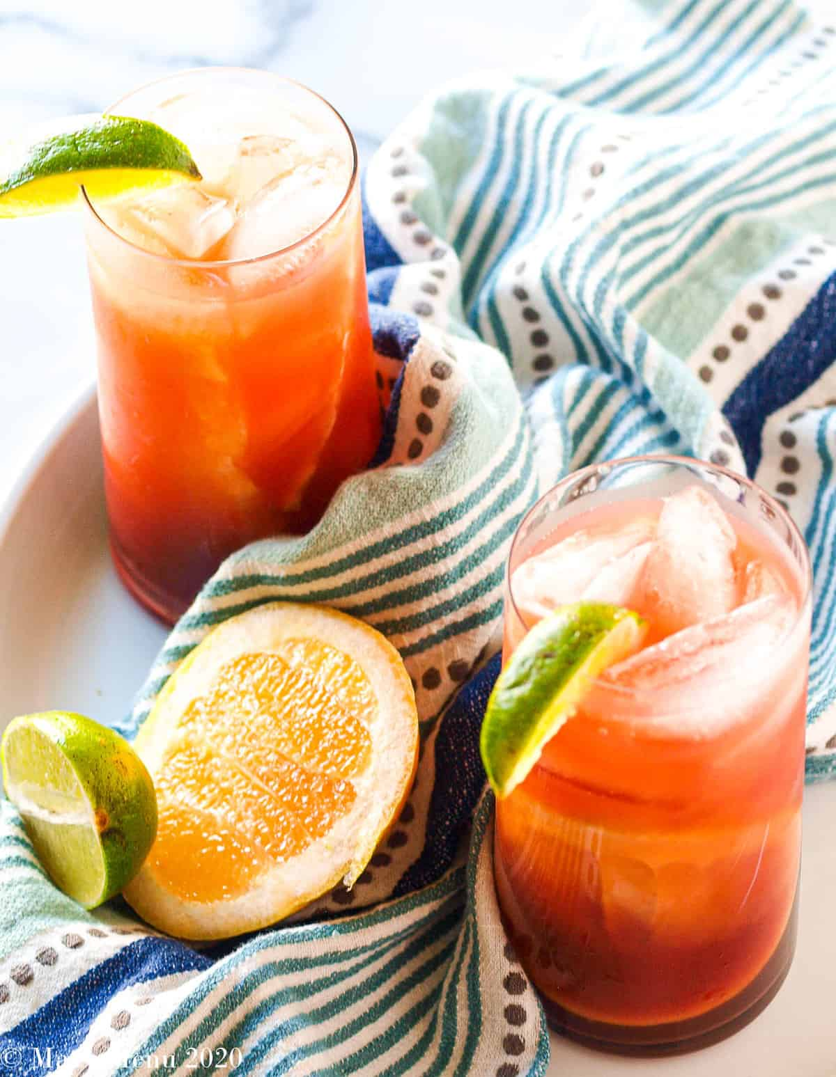 an overhead shot of 2 glasses of pomegranate sea breeze cocktails on a white platter with a blue striped towel. a wedge of grapefruit and lime sit between the cups