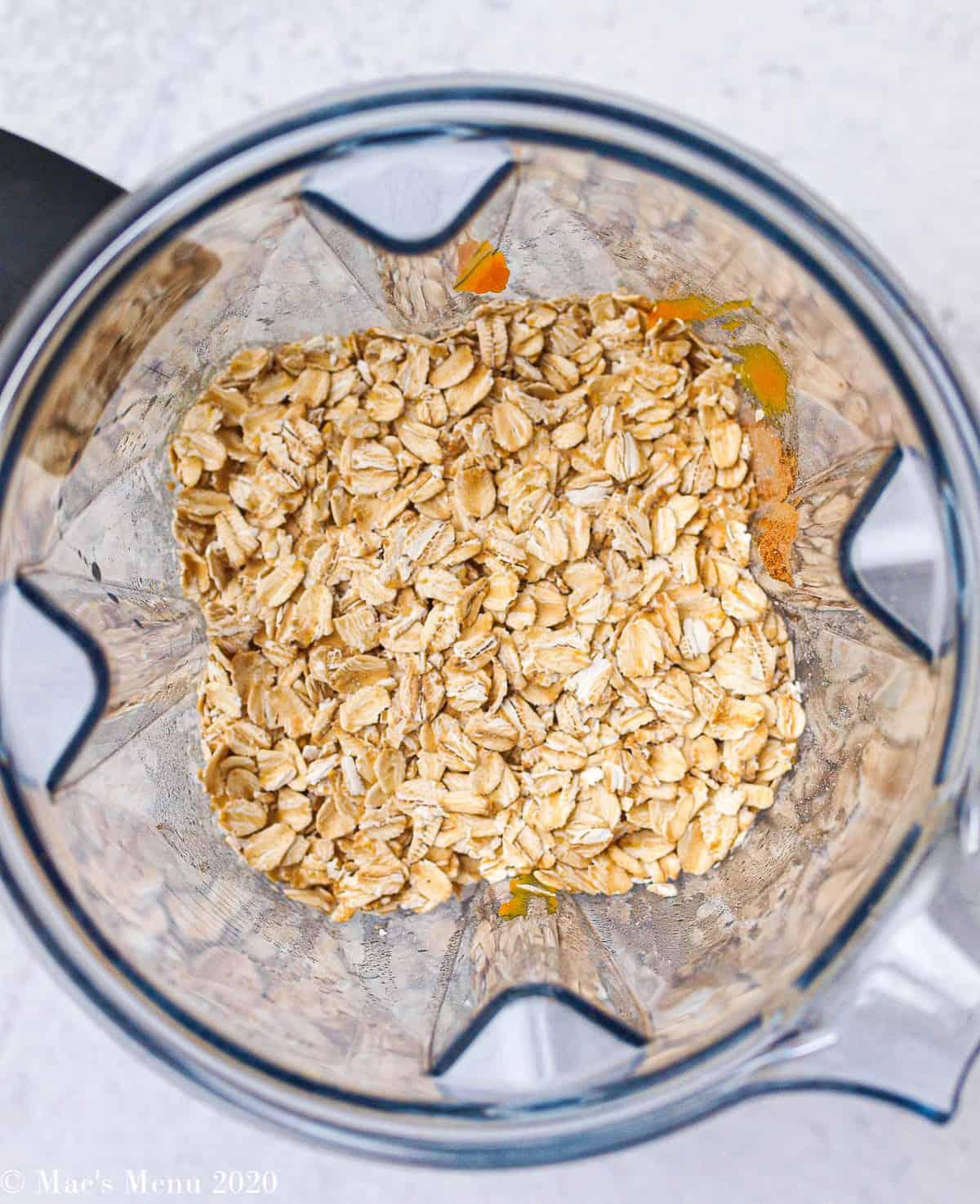 An overhead shot of oats and pumpkin in a vitamix blender pitcher