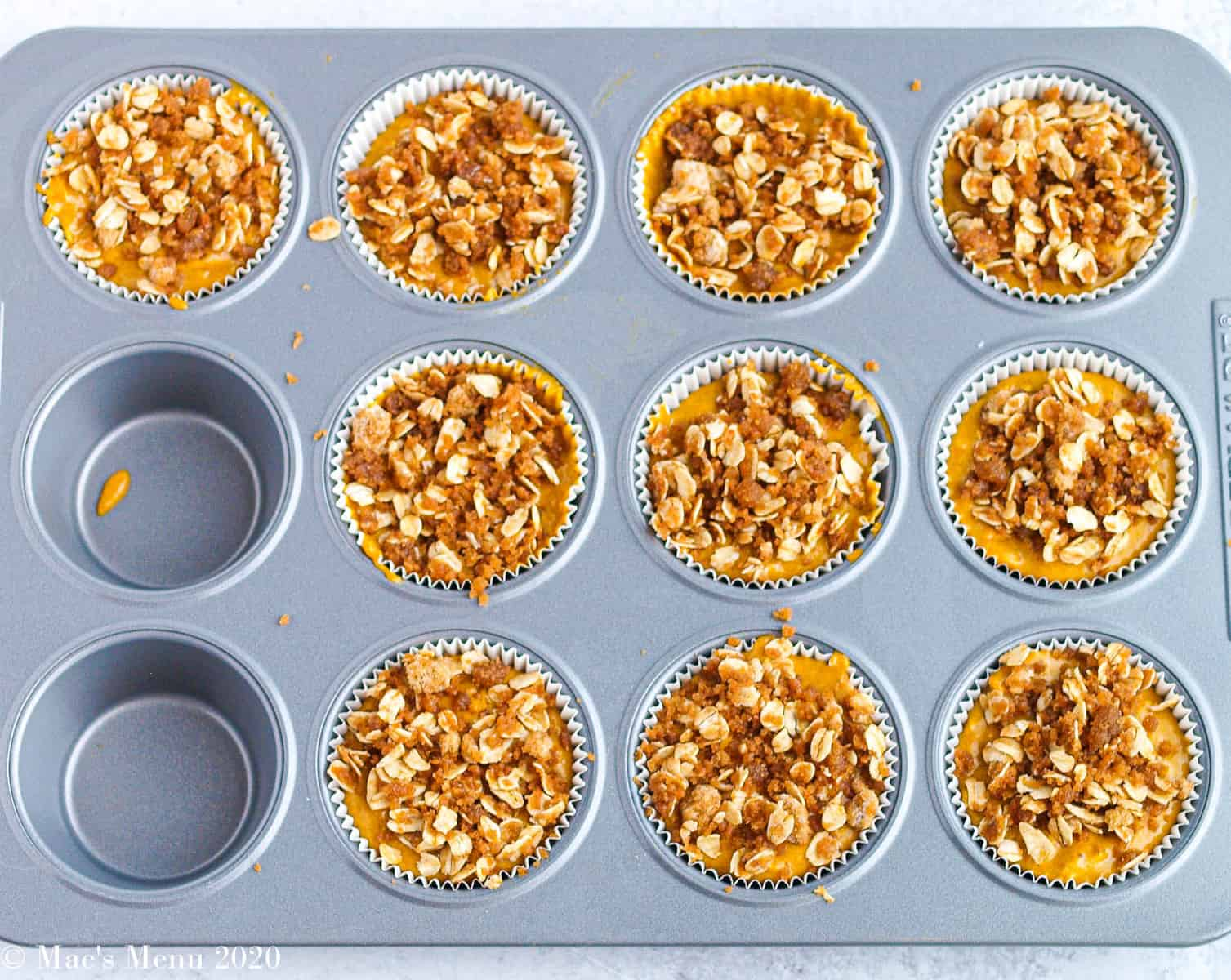 A muffin tin with pumpkin muffins with streusel on top before baking
