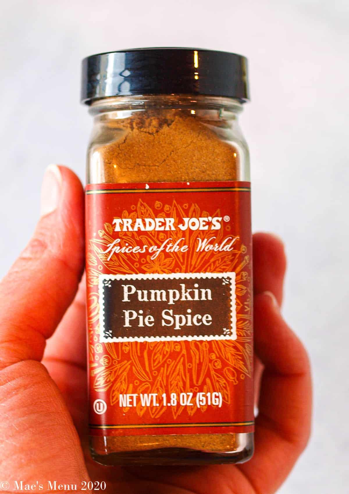 An upclose shot of a hand holding trader joe's pumpkin pie spice