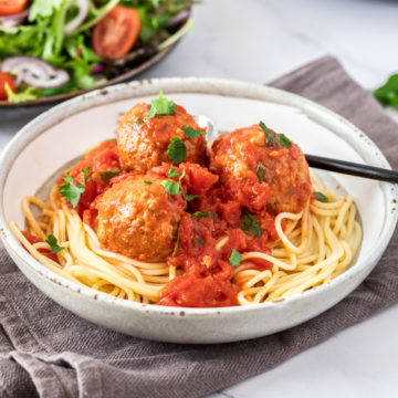 Healthy Turkey meatballs on a small bowl of pasta next to a small dish of salads