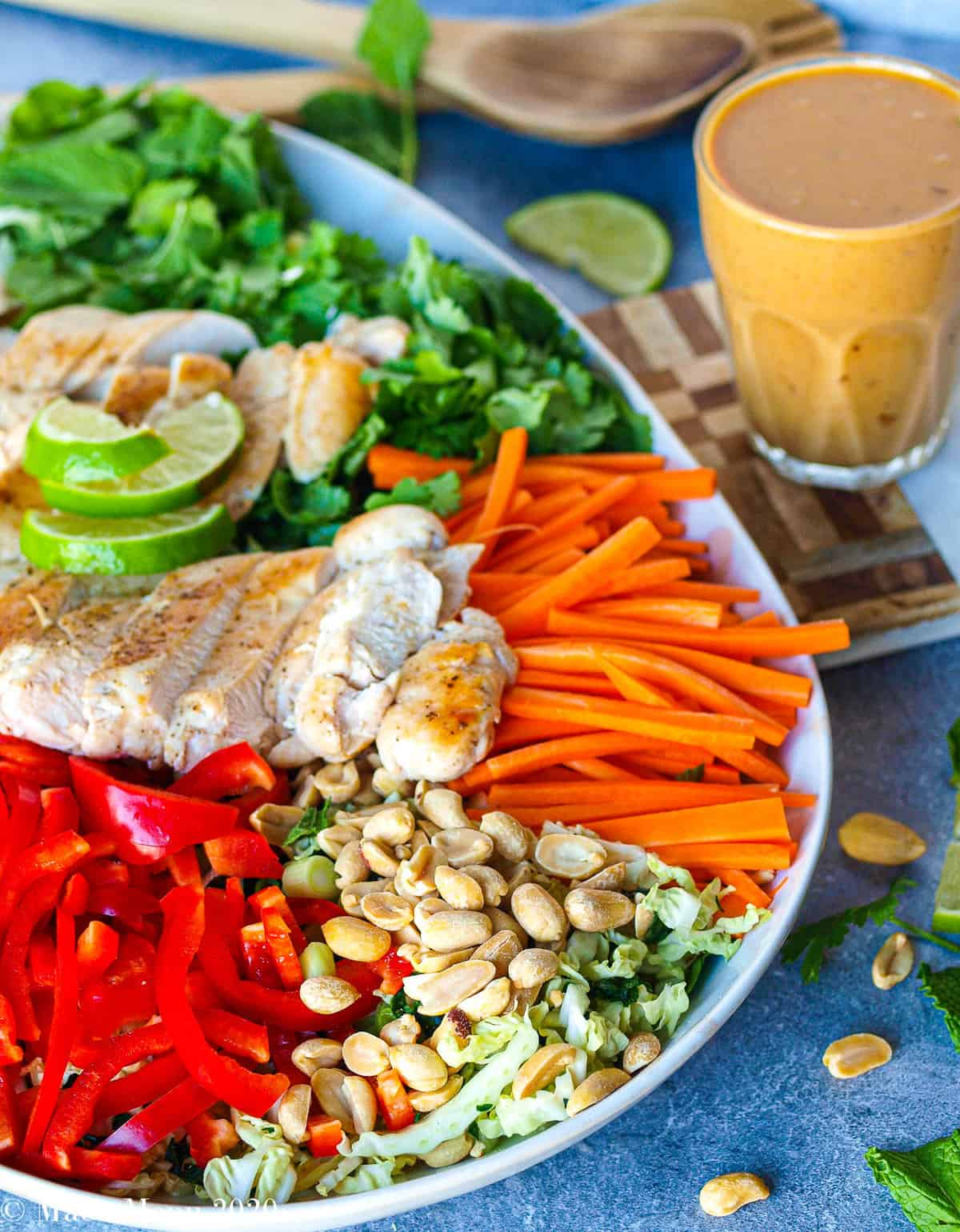 A side-angle shot of thai chicken salad with a cup of dressing on the side of the platter and the salad tongs in the background