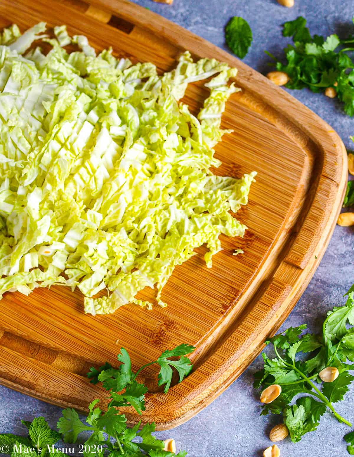 An overhead shot of half of head of napa cabbage sliced on a wooden cutting board with herbs and peanuts around the chopping board