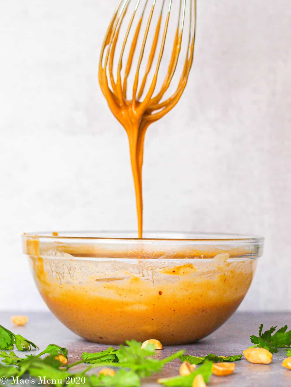 A side shot of a clear bowl of dressing with a whisk drizzling the dressing into the bowl