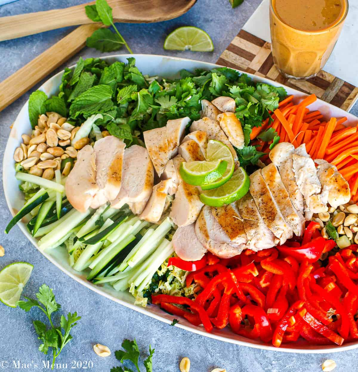 An overhead shot of a platter of thai chicken salad with peanut dressing. Besides the platter sits the cup of dressing. To the top of the platter sits the salad tongs. Chopped herbs, lime, and peanuts sit around the platter