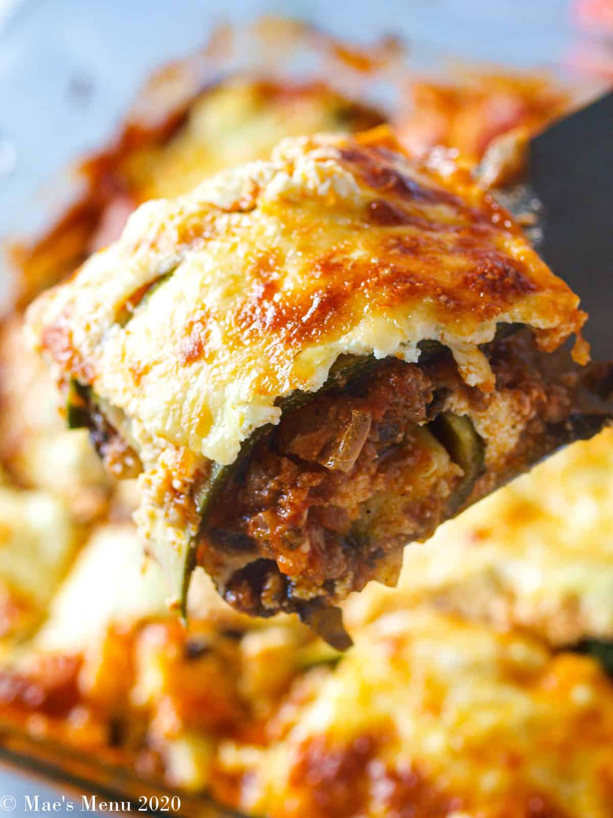 A large scoop of zucchini lasagna over a tray of lasagna