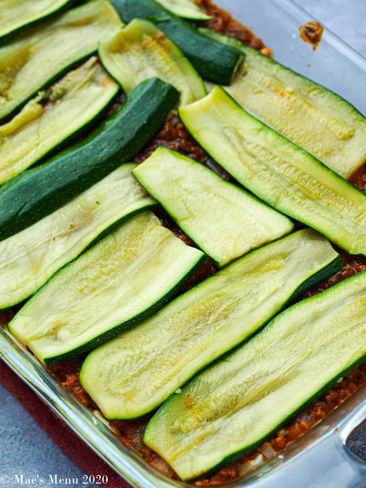 Slices of zucchini on top of the meat pasta sauce as we build the lasagna