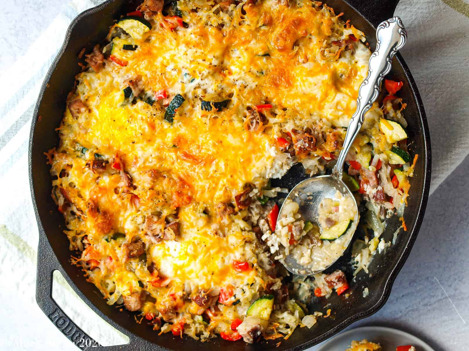 An overhead shot of a mountain breakfast skillet with a large spoonful taken out of it.