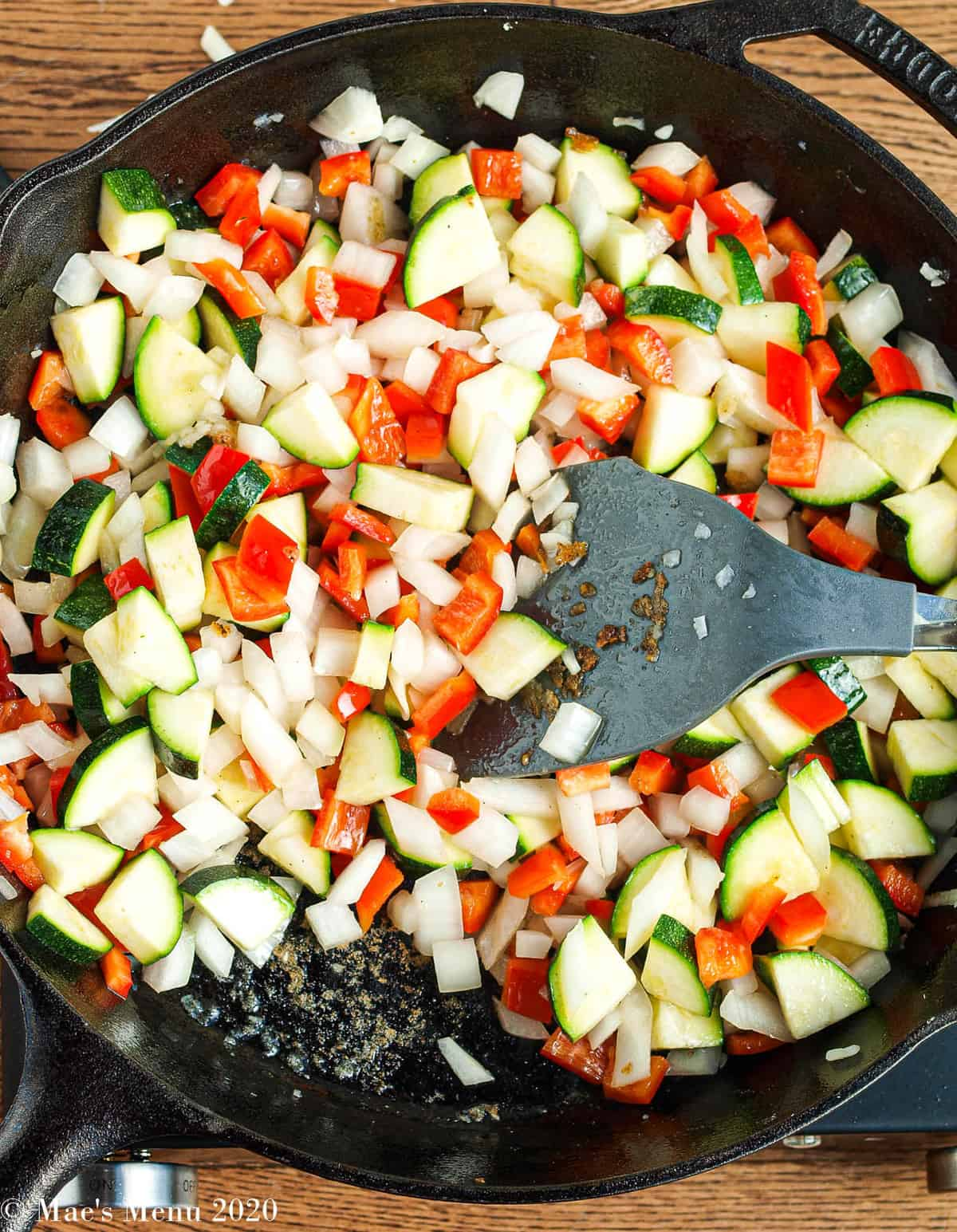 An overhead shot of a cast iron skillet with chopped peppers, onion, and zucchini