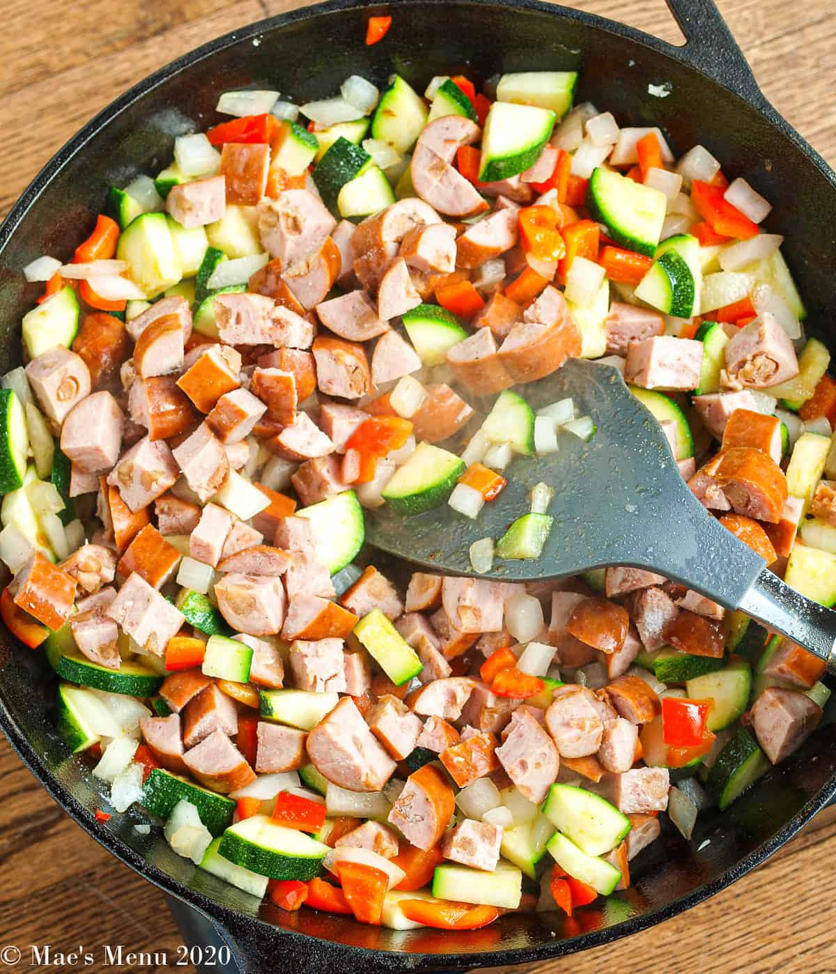 A cast iron skillet with cubed sausages, peppers, zucchini, and onion in it