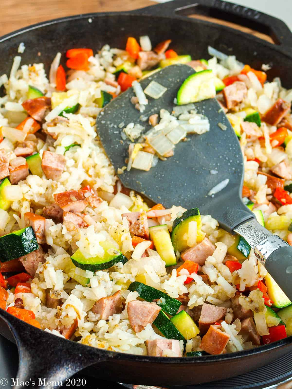 A side shot of a cast iron skillet with shredded hash browns, zucchini, peppers, sausage, and onions in it
