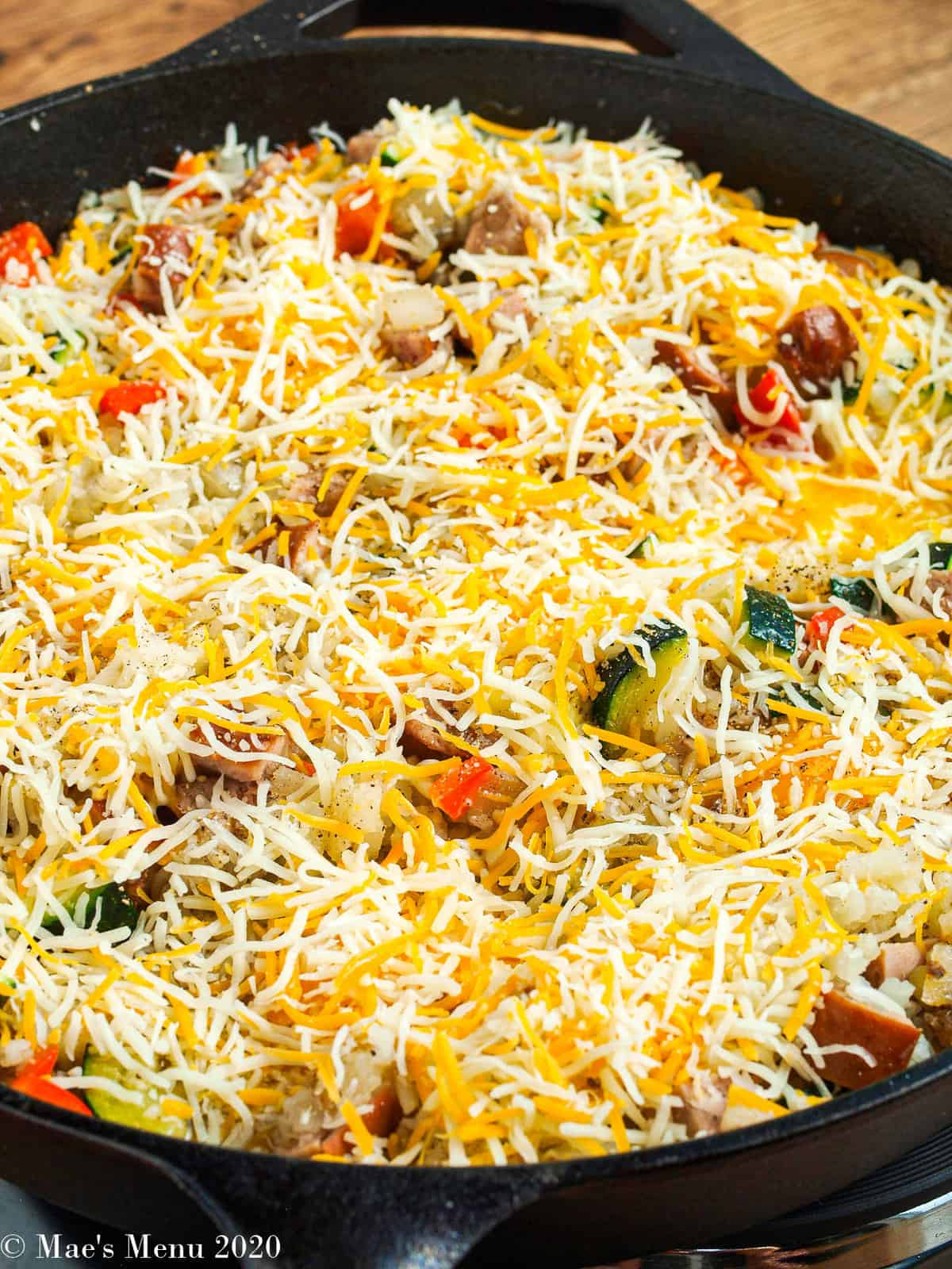 A side shot of the breakfast skillet with fresh shredded cheese on top.