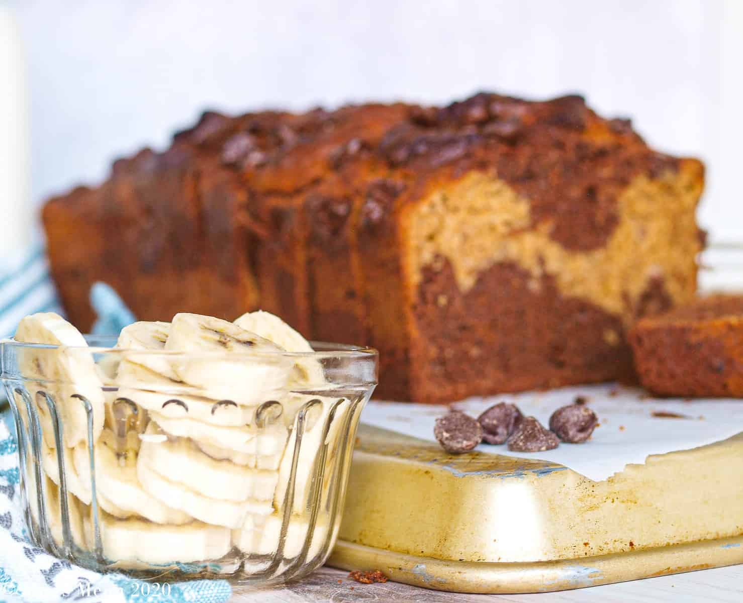 A sliced loaf of chocolate peanut butter banana bread on a gold pan with a dish of sliced bananas and chocolate chips next to it