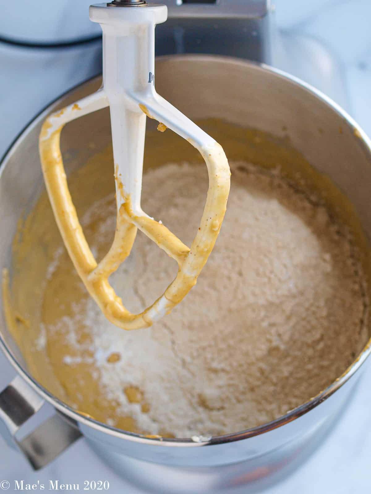 Adding white whole wheat flour to the bowl of batter