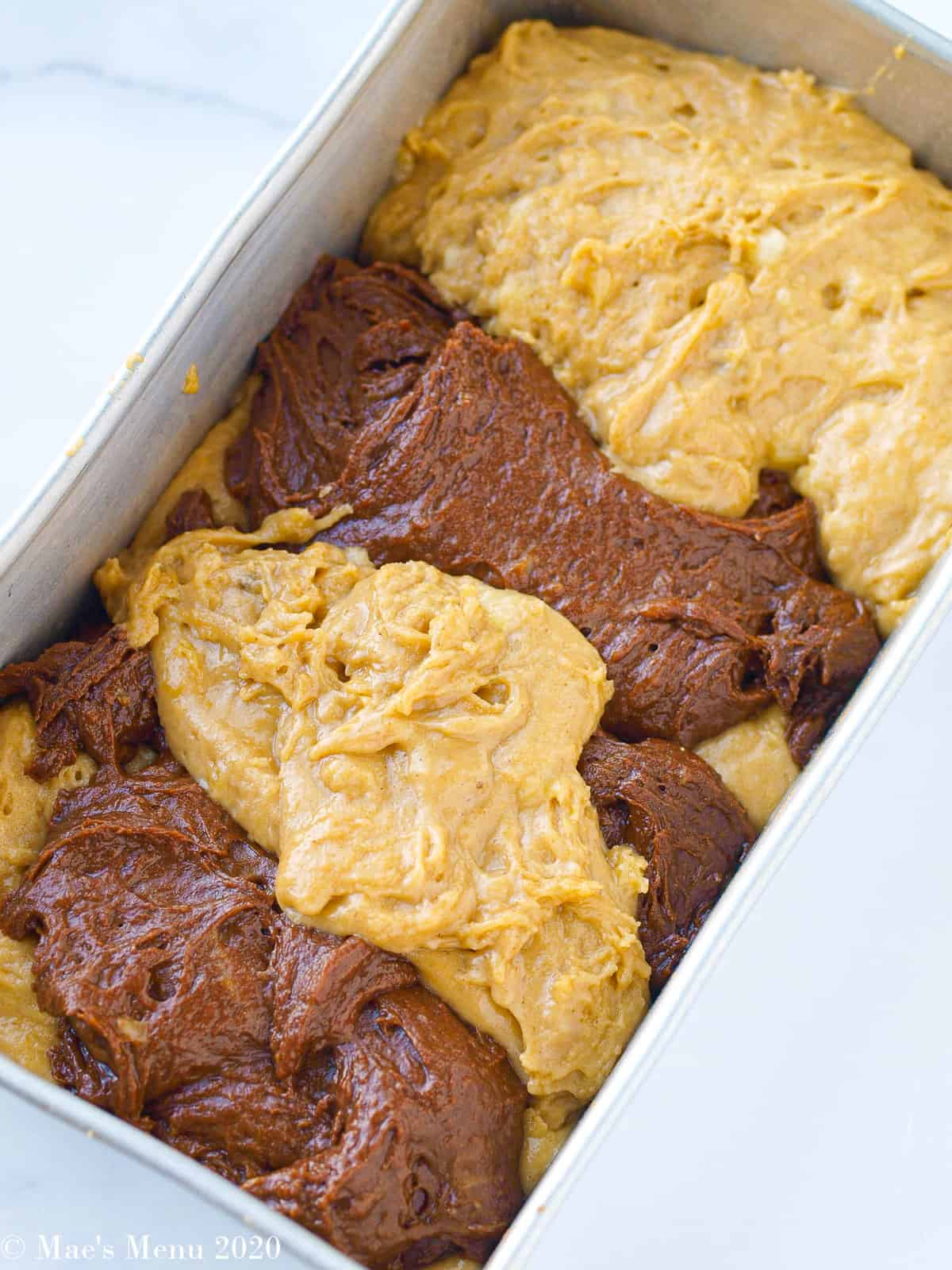 Scoops of the banana bread batter scattered throughout a loaf baking pan