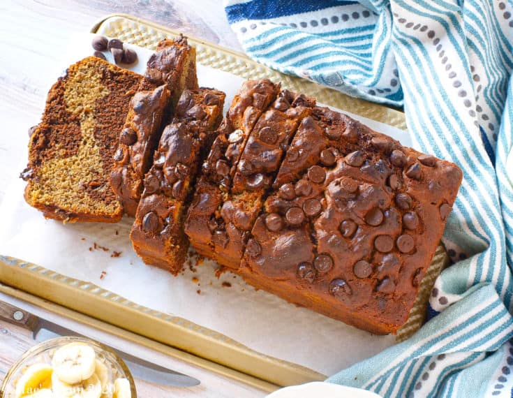 An overhead shot of a loaf of chocolate peanut butter banana bread sliced on a cutting board