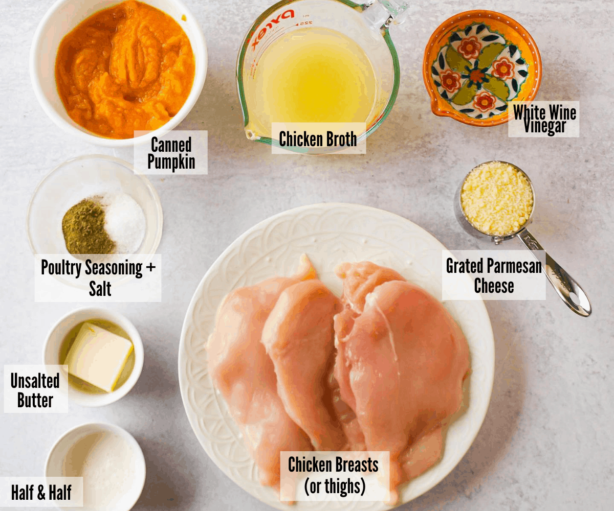 All the ingredients for parmesan pumpkin chicken: canned pumpkin, chicken broth, white wine vinegar, grated parmesan cheese, chicken breasts, poultry seasoning and salt, unsalted butter, and half & half