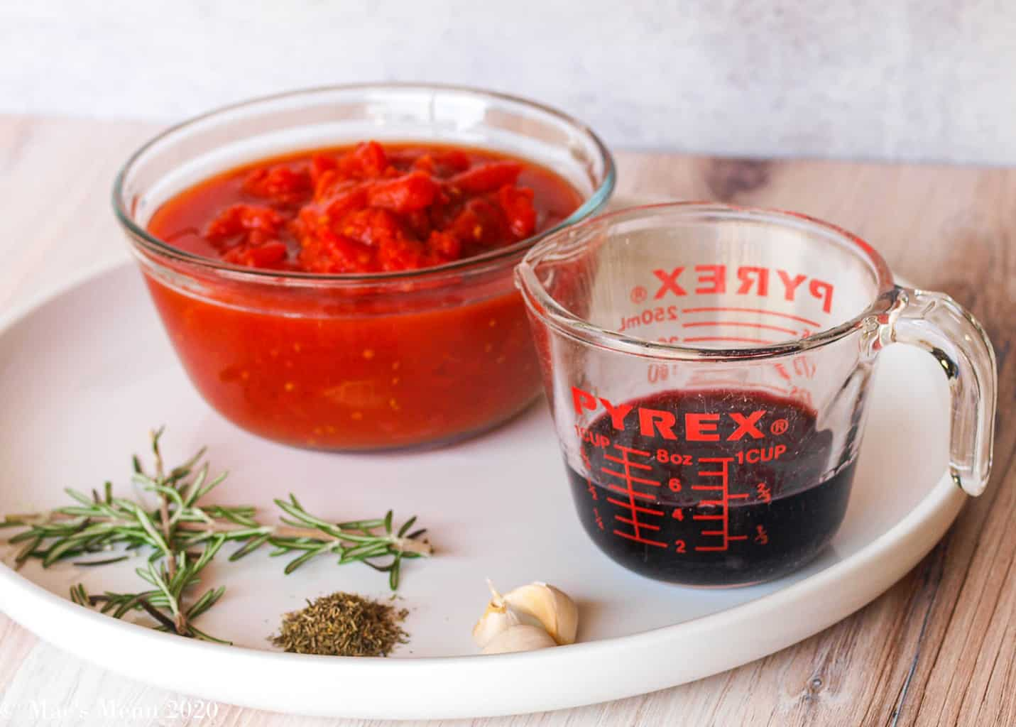Canned tomatoes, red wine, and herbs for the pressure cooker beef ragu