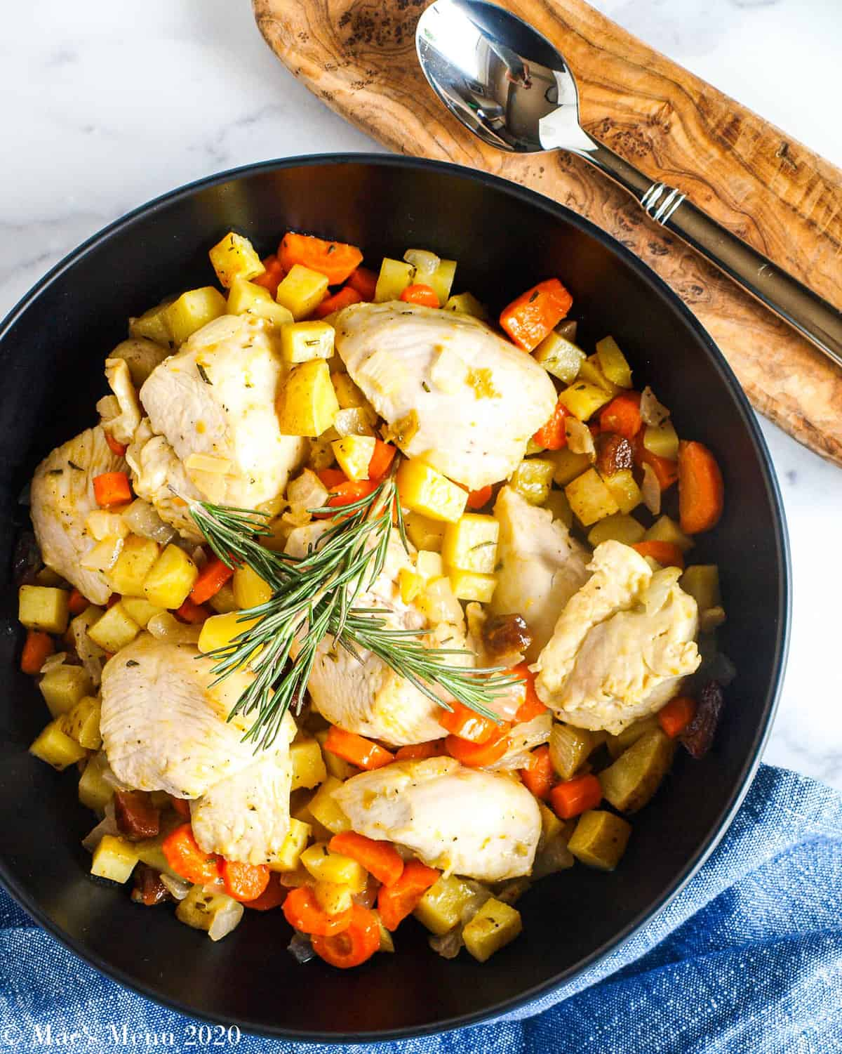 An overhead shot of a large black serving bowl of sheet pan apricot chicken next to a blue towel and wooden spoon holder