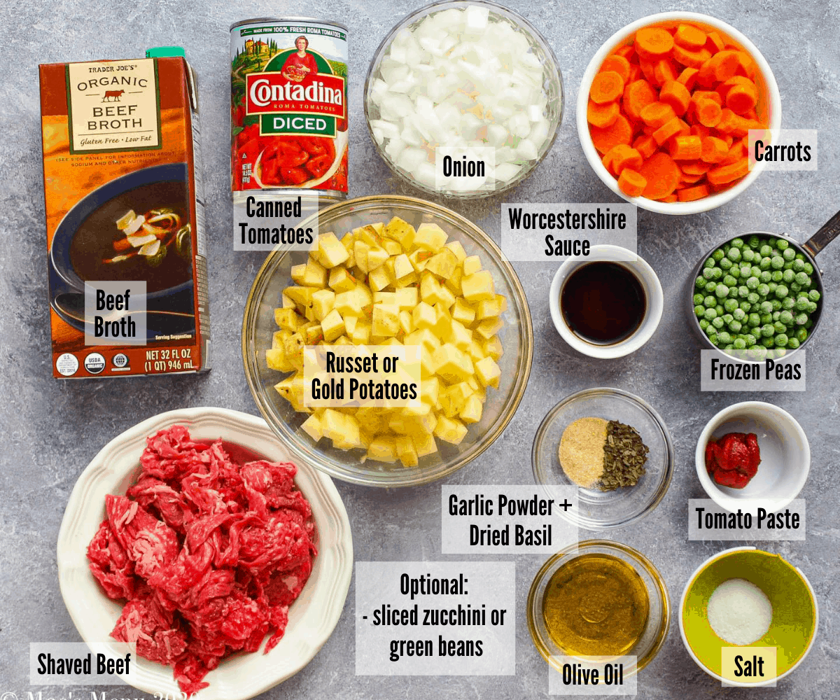 All of the ingredients for this steak soup  laid out on a concrete counter top.