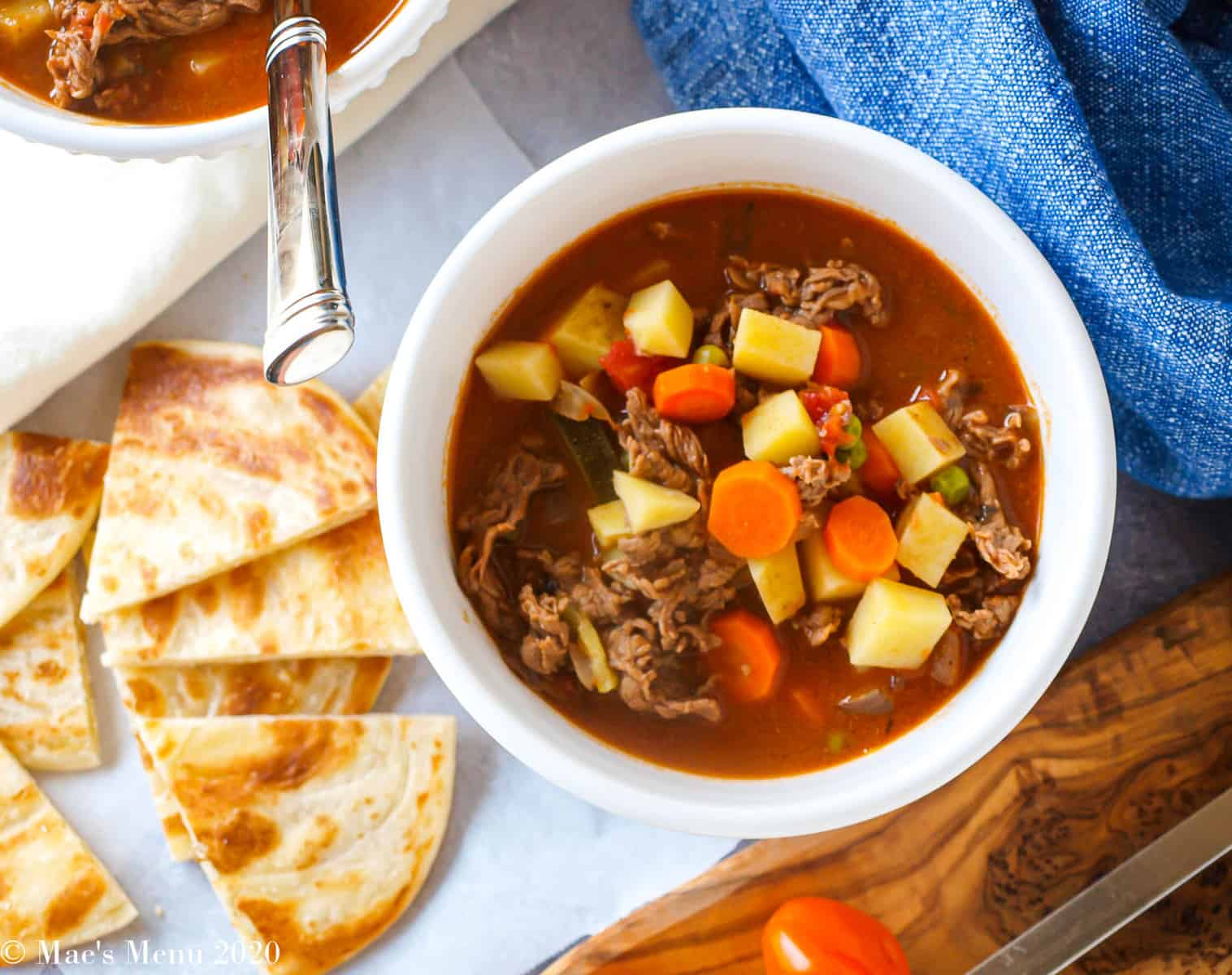 An overhead shot of a bowl of steak soup next to pita pieces, baby tomatoes, and tea towels