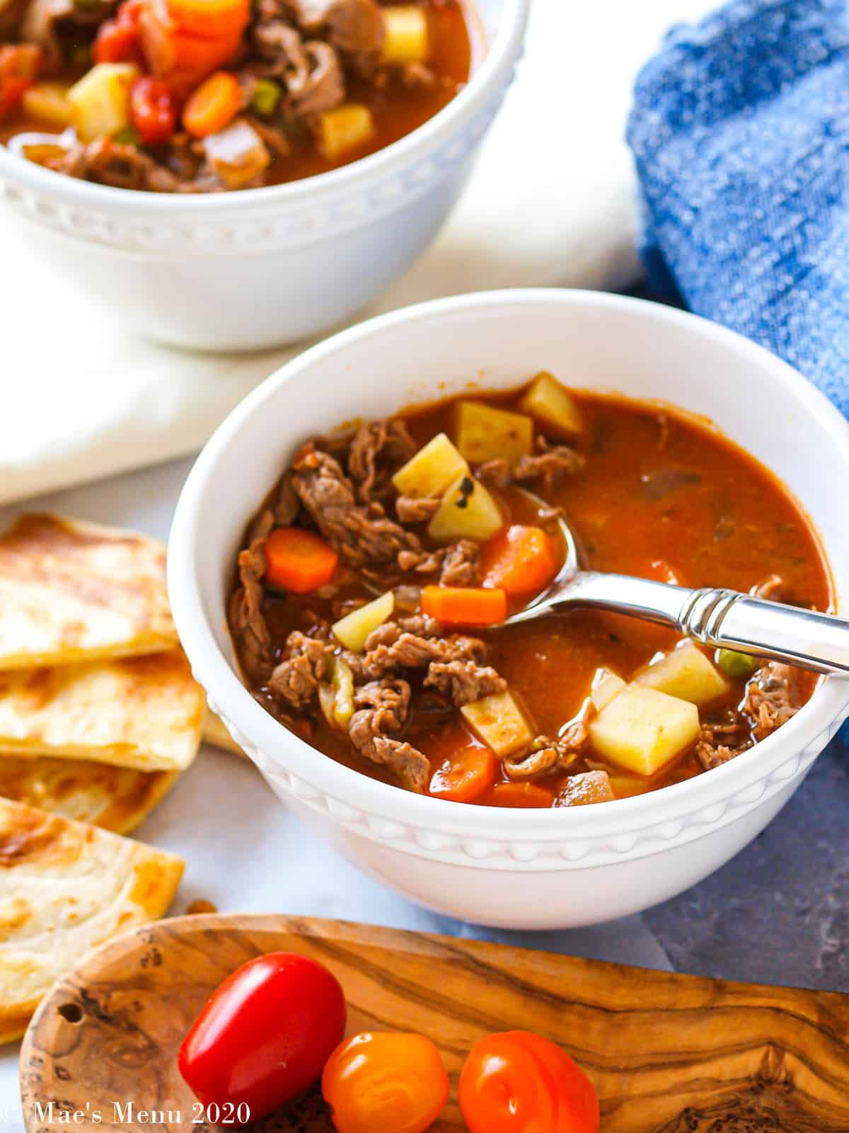 A side angle shot of two white bowls of steak soup with baby tomatoes and pita chips next to it