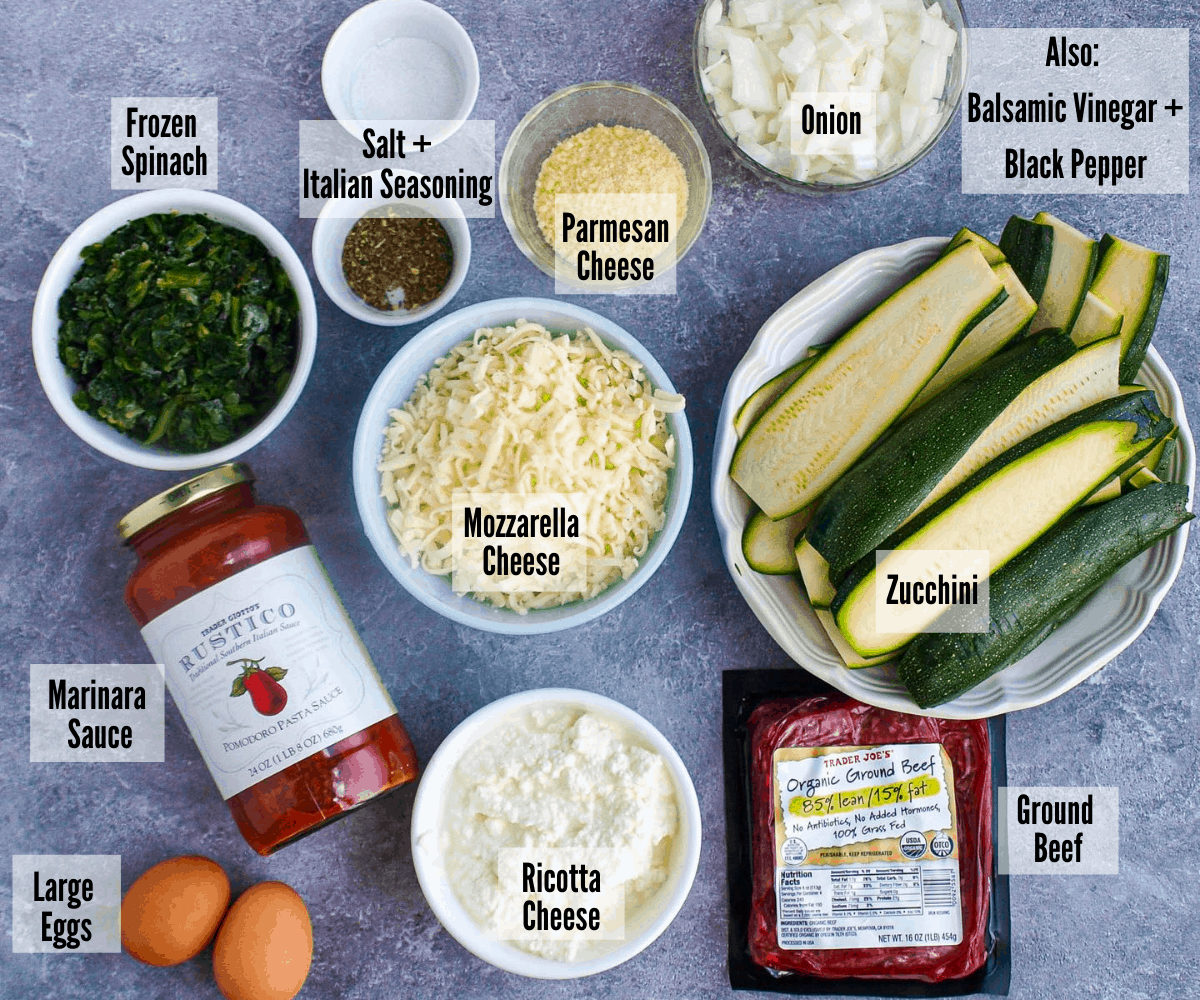 All the ingredients for the zucchini lasagna -- frozen spinach, salt and italian seasoning, parmesan cheese, onion, balsamic vinegar + black pepper, zucchini, ground beef, ricotta cheese, marinara sauce, and large eggs