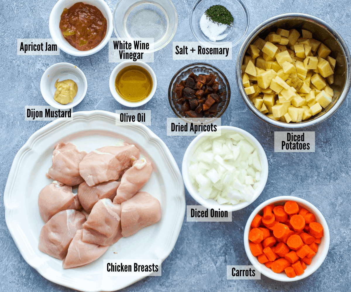 All the ingredients for sheet pan apricot chicken and vegetables: apricot jam, white wine vinegar, salt and rosemary, dijon mustard, olive oil, dried apricots, diced potatoes, chicken breast, onions, and carrots