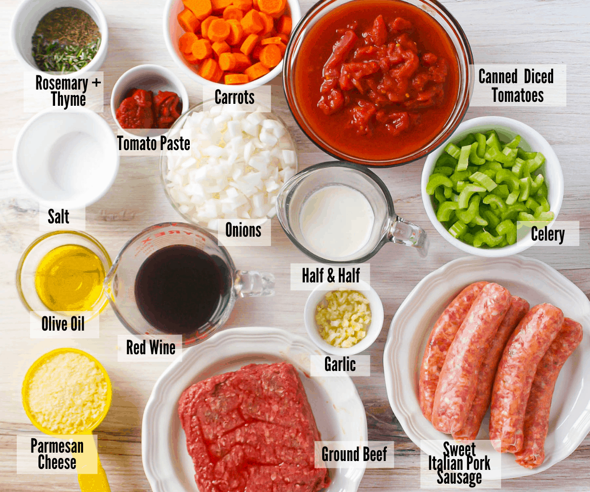 All the ingredients for pressure cooker beef ragu: rosemary & thyme, tomato paste, carrots, canned diced tomatoes, salt, onions, half & half, celery, olive oil, red wine, garlic, sweet Italian pork sausage, ground beef, and parmesan cheese