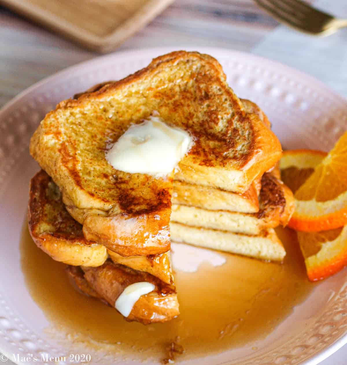 A side angle shot of a large stack of brioche french toast with a wedge taken out