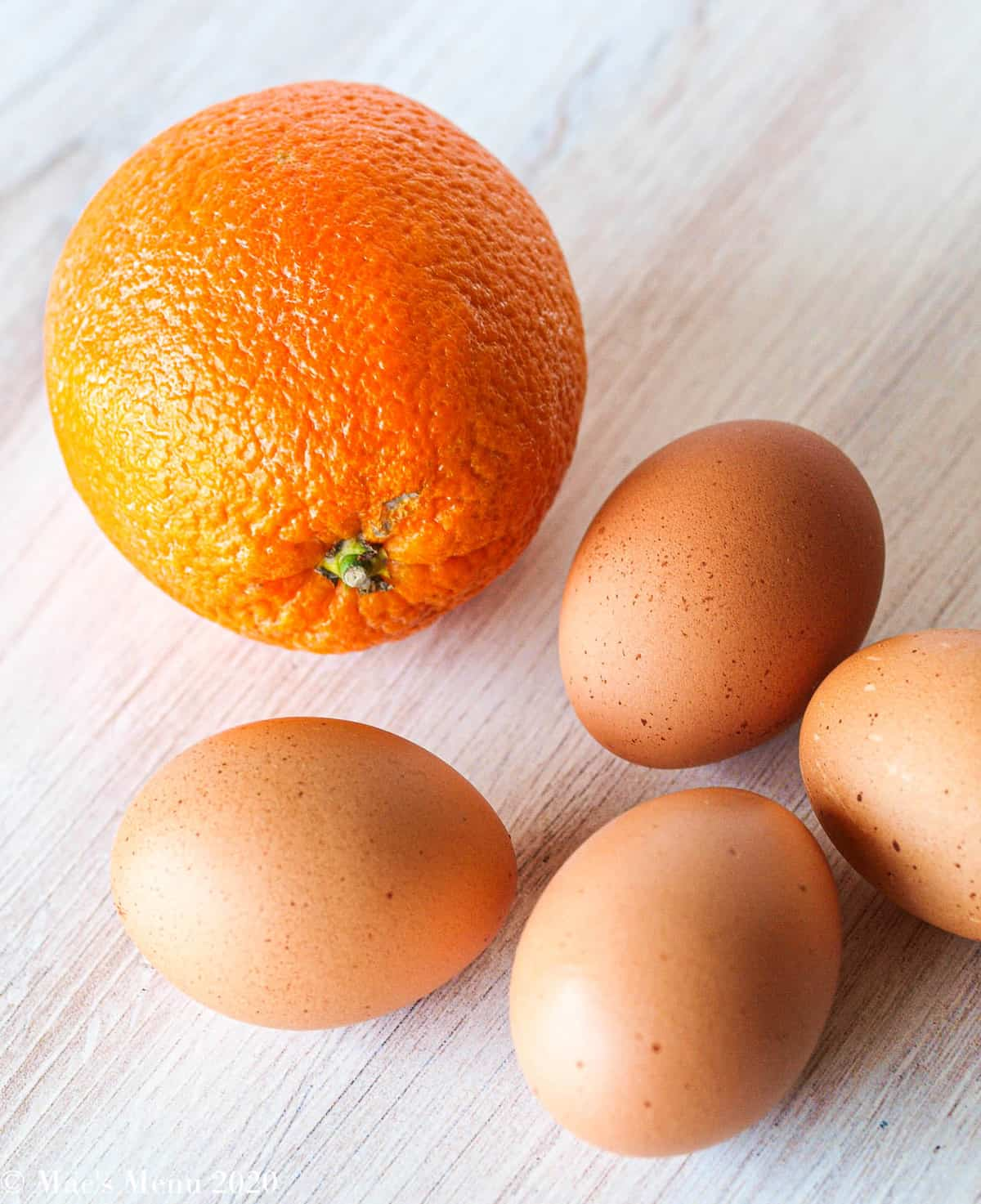 An orange next to 4 large brown eggs