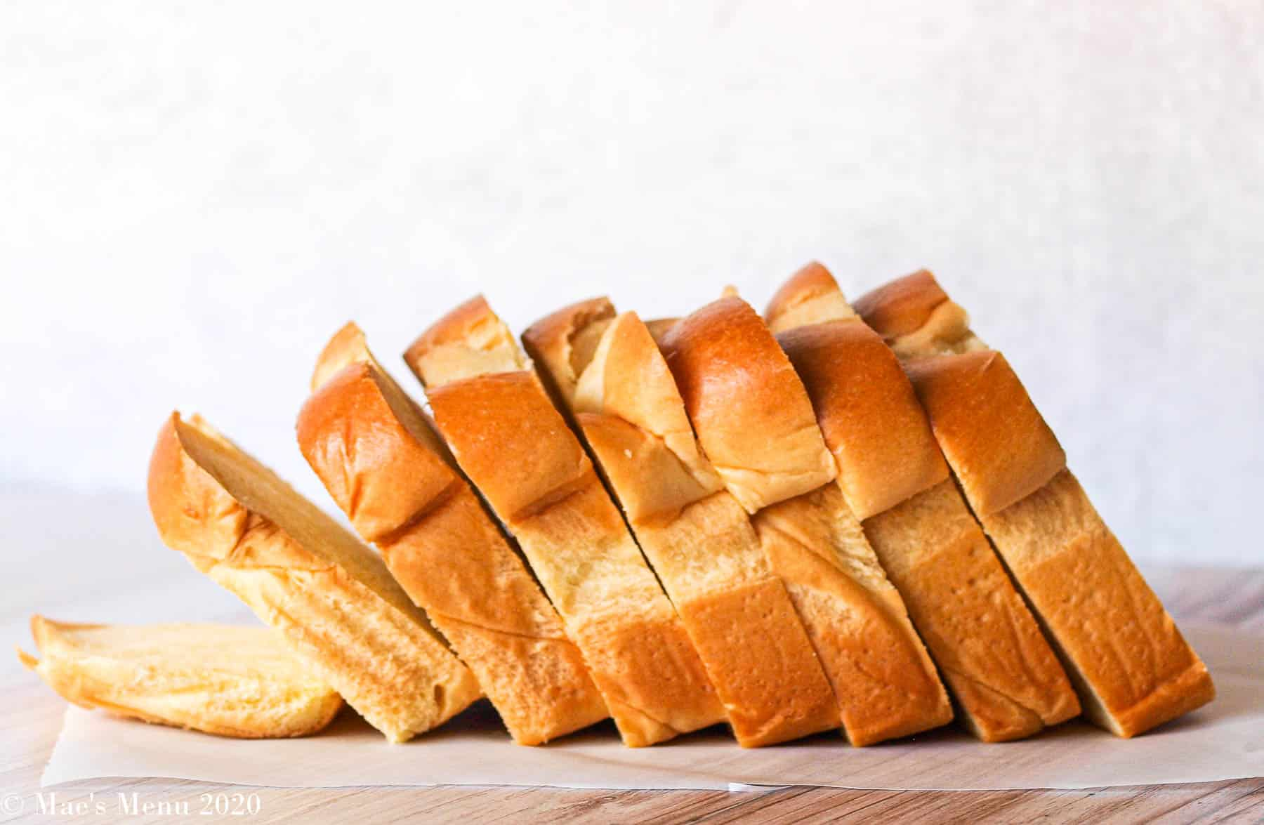 A loaf of brioche bread sitting on a counter on a piece of parchment paper