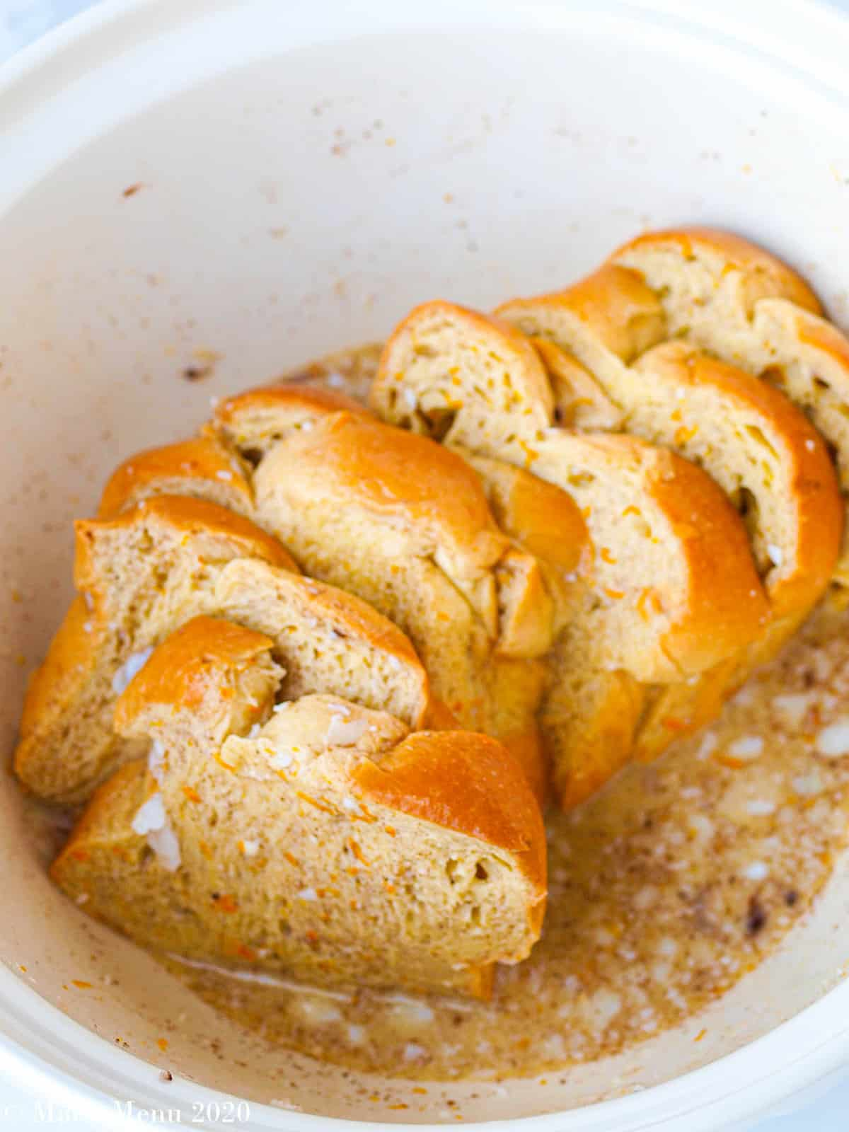 Brioche bread soaking in the egg mixture in a large white mixing bowl