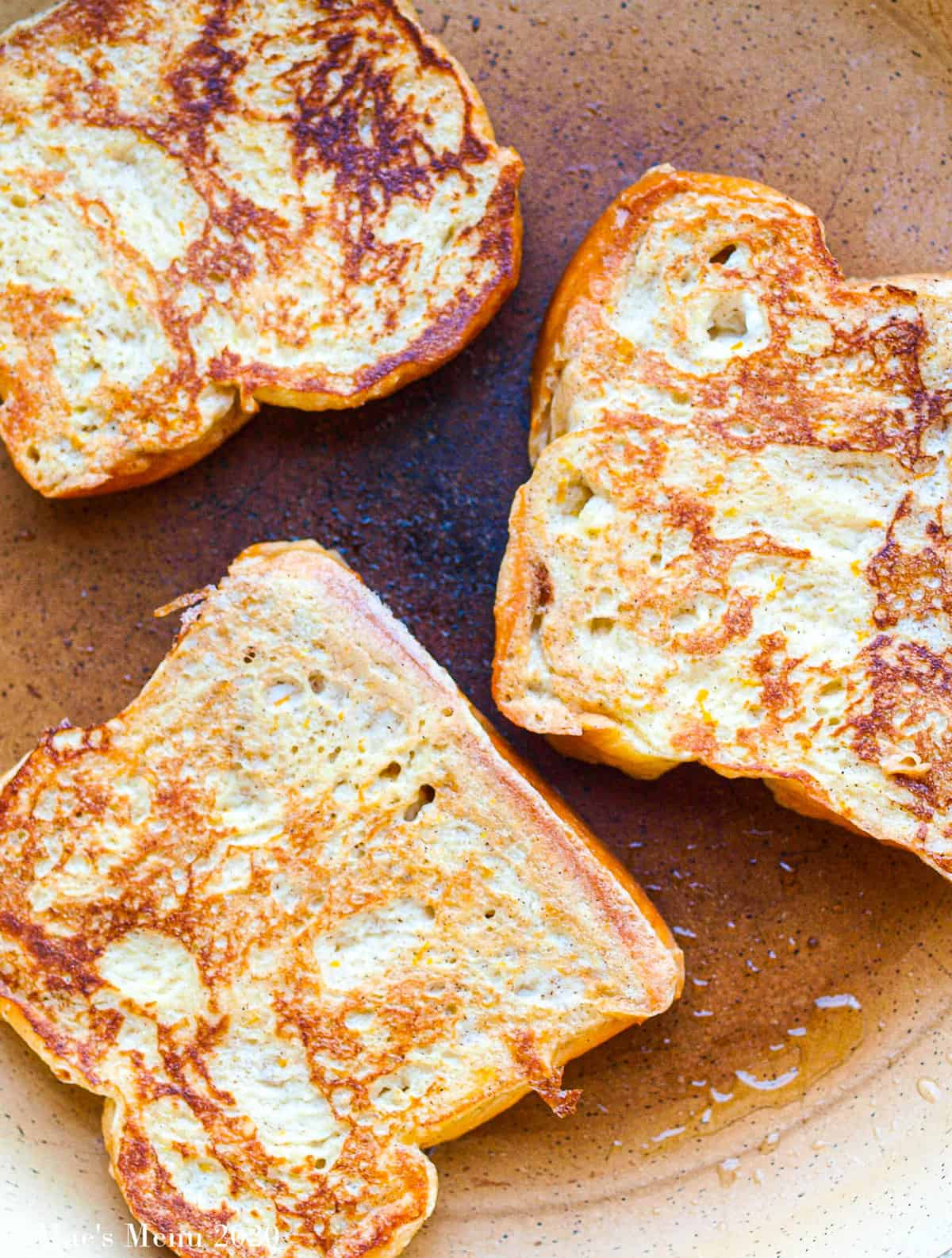 3 pieces of french toast cooking on a non-stick skillet