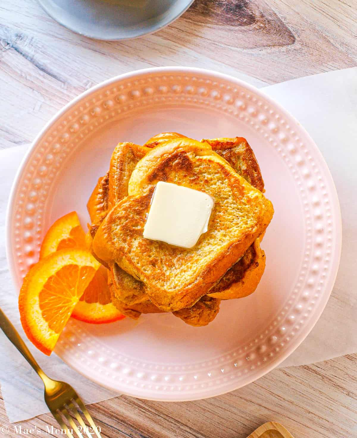 An overhead shot of a large stack of brioche french toast with a square of butter on top and orange slices on the side
