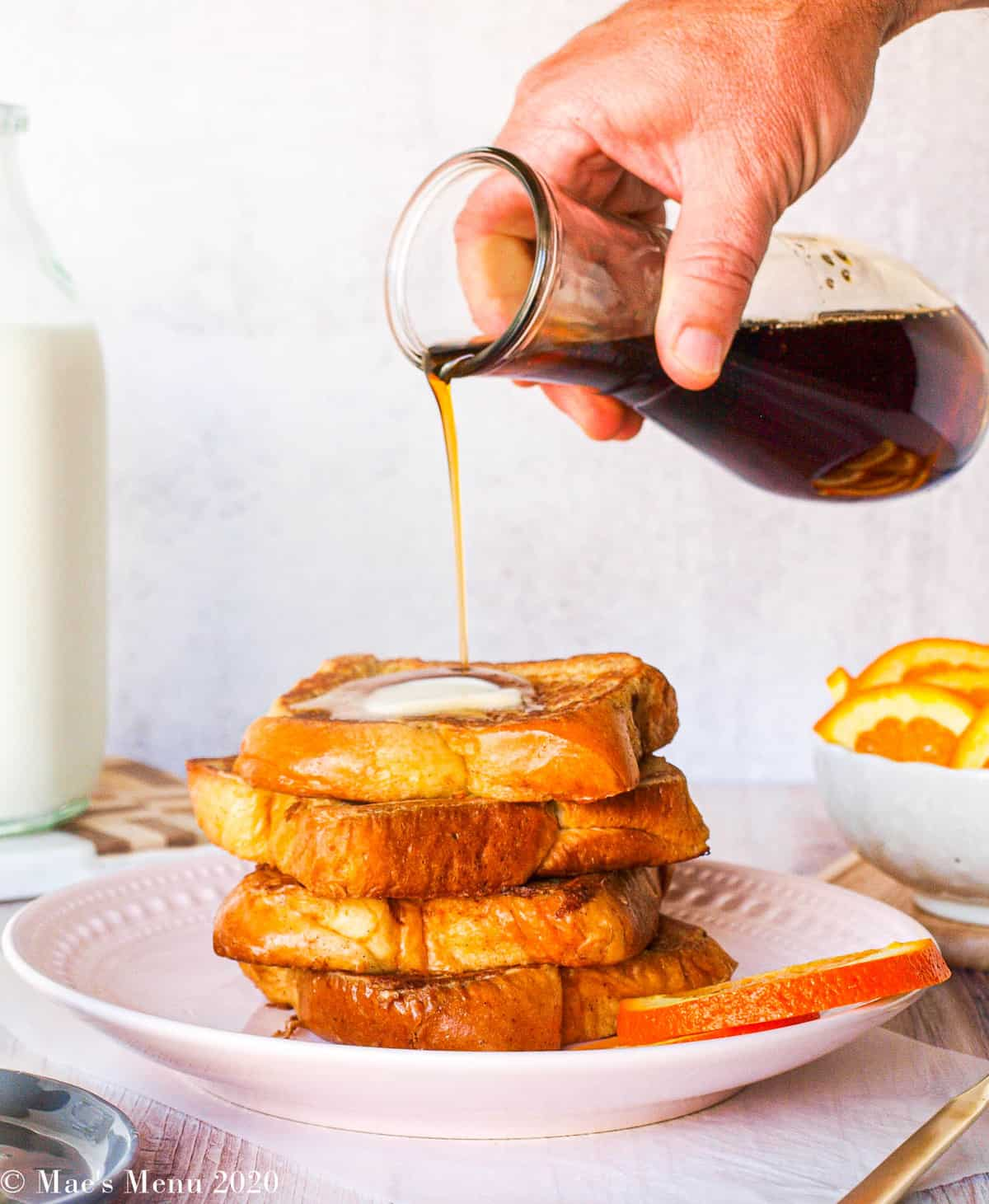 A large stack of brioche french toast with a hand pouring maple syrup on top