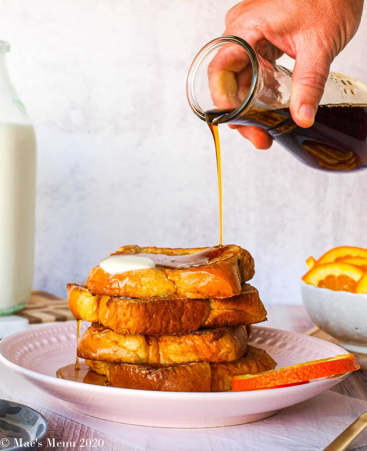A hand pouring maple syrup over a large stack of brioche french toast. Extra maple syrup is pouring off the sides of the toast