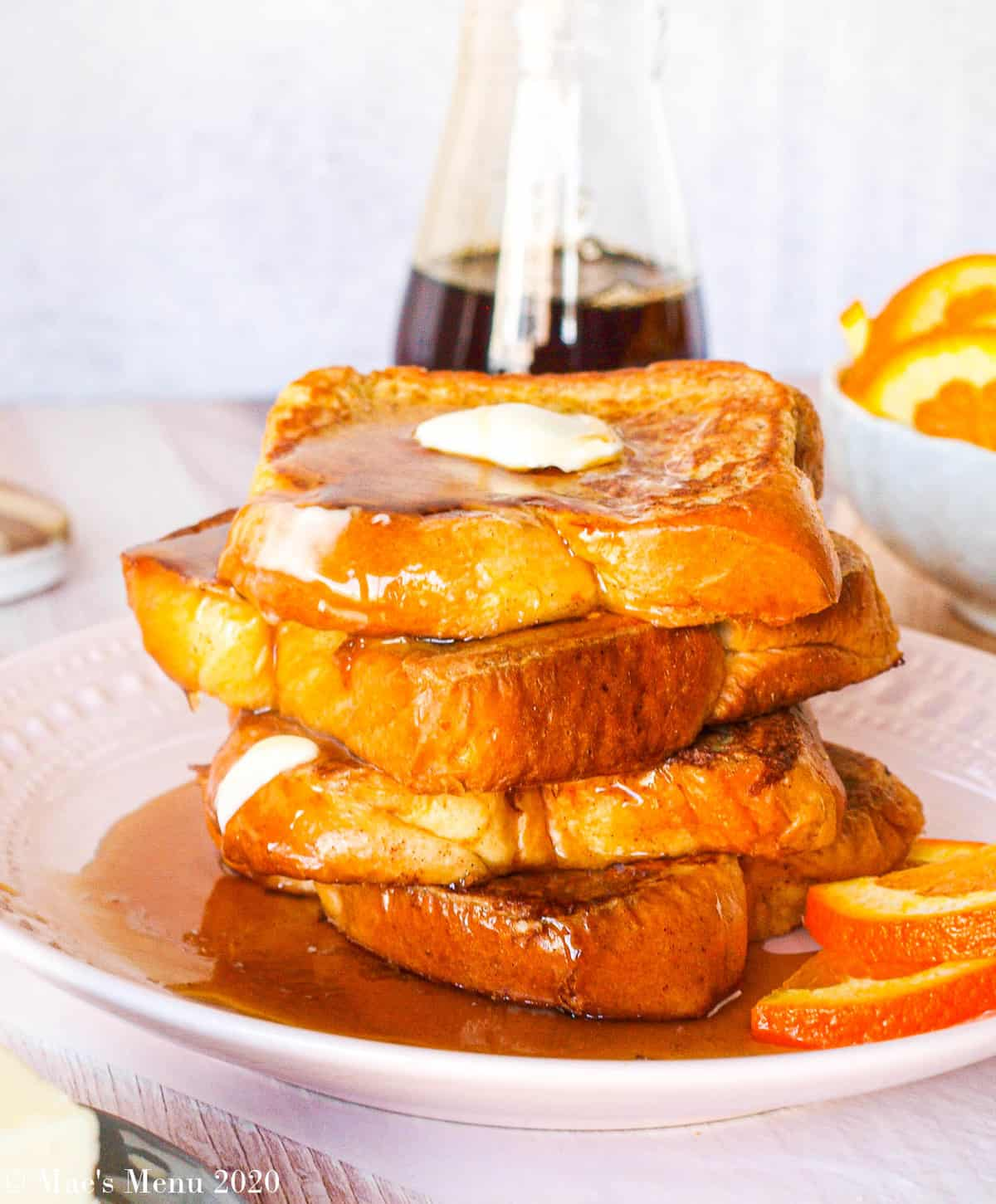 An up-close shot of a large stack of brioche french toast with butter and maple syrup on top